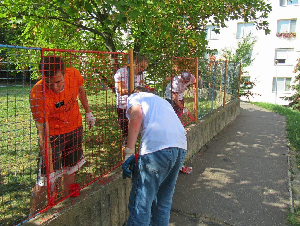 Dobrovoľníci natierajú plot